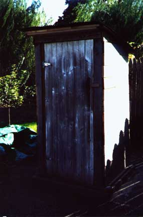 The homemade outhouse with the door closed