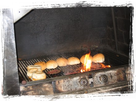 Burgers being grilled over hot charcoal