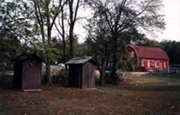 An Apple Orchard Pair of Outhouses