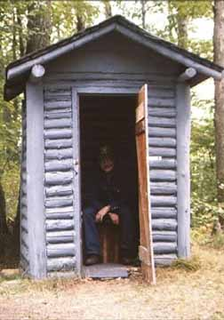 The Proud Owner of the Log Outhouse